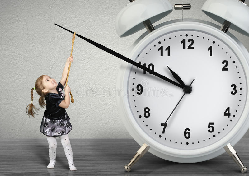 Pequeño niño que tira del reloj de la mano, concepto de la gestión de tiempo fotos de archivo libres de regalías