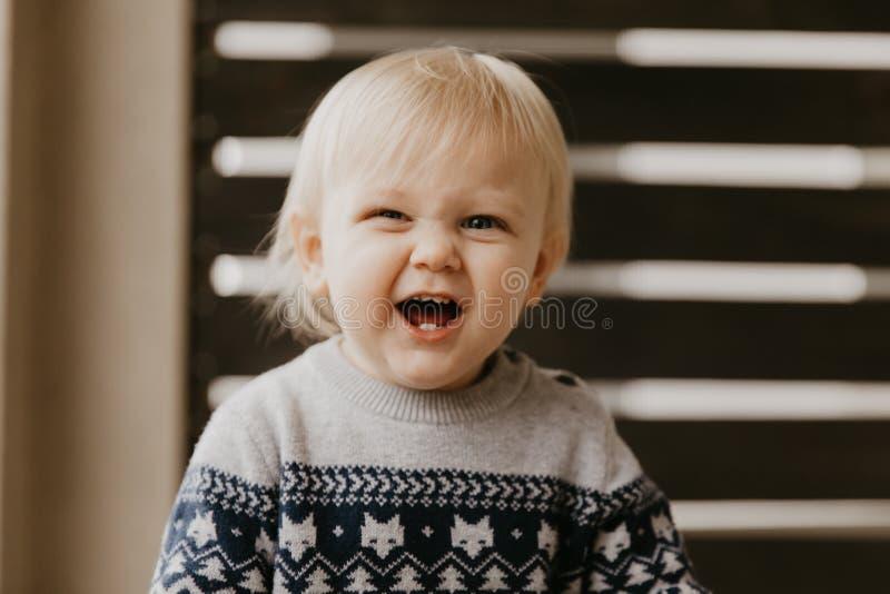 Pequeño niño rubio adorable lindo del niño que ríe, divirtiéndose, y haciendo caras tontas afuera en casa en el pórtico defendido imagen de archivo libre de regalías