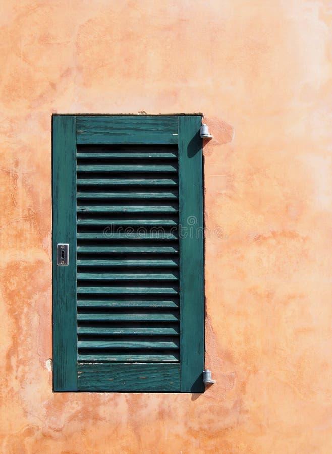 Pequeño obturador de madera cerrado pintado verde en una pared texturizada áspera vieja anaranjada ocre en luz del sol brillante  fotografía de archivo libre de regalías