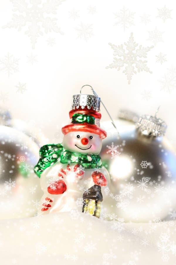 Pequeño ornamento del muñeco de nieve en la nieve fotografía de archivo