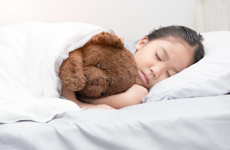 Pequeño oso de peluche asiático lindo del sueño y del abrazo de la muchacha imagen de archivo libre de regalías