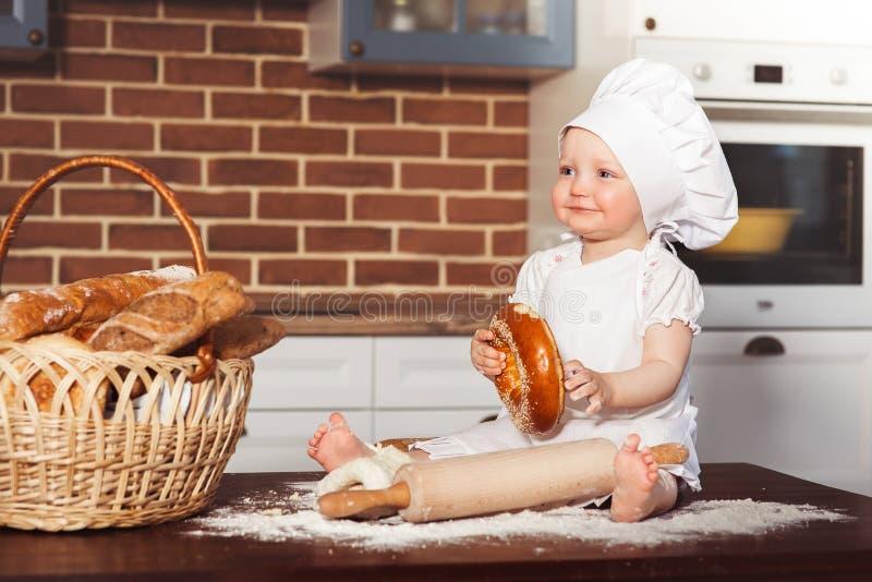Pequeño panadero sonriente del bebé en el sombrero y el delantal blancos del cocinero imagen de archivo