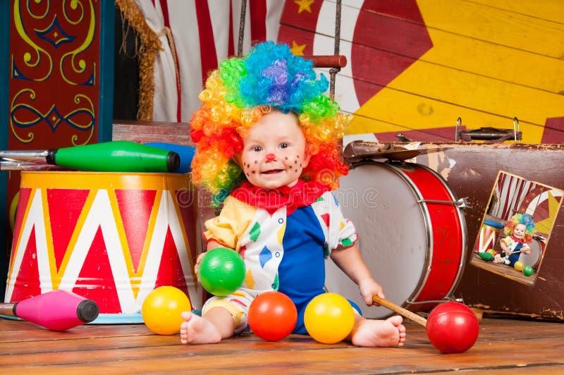 Pequeño payaso del bebé con la peluca multicolora de la nariz roja adentro con las bolas imagenes de archivo