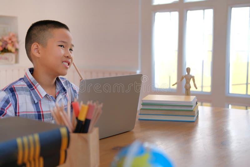 pequeño pensamiento asiático joven del colegial de los niños del niño del muchacho del niño imagenes de archivo