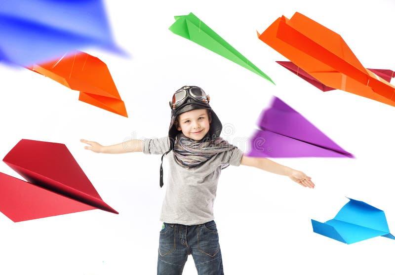 Pequeño piloto lindo entre los aviones de papel coloridos fotografía de archivo libre de regalías