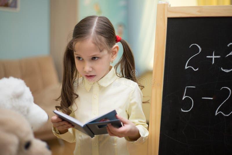 Pequeño profesor La chica joven hermosa está enseñando a los juguetes en casa en la pizarra foto de archivo