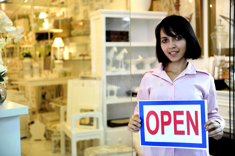 Pequeño propietario de negocio: mujer que lleva a cabo una muestra abierta