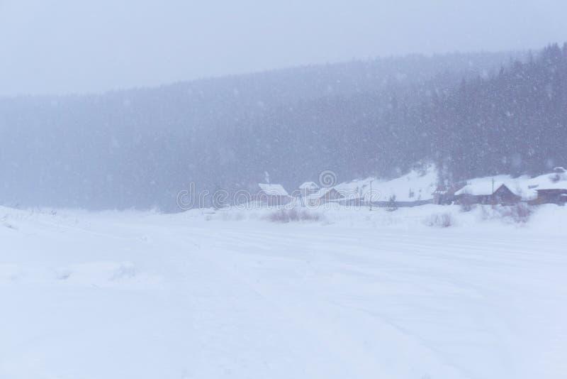 Pequeño pueblo en el banco del río durante nevadas imagen de archivo libre de regalías