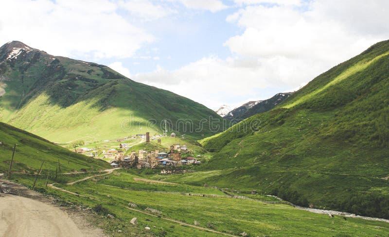 Pequeño pueblo en el Cáucaso con las torres de piedra de la defensa al lado de un río en un valle Ushguli en Georgia foto de archivo