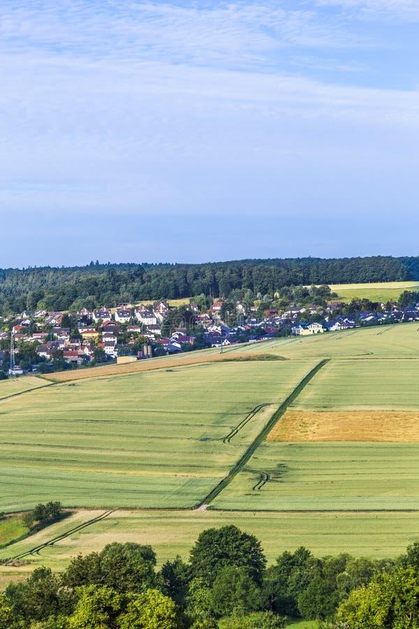 Pequeño pueblo en el Taununs con los campos foto de archivo