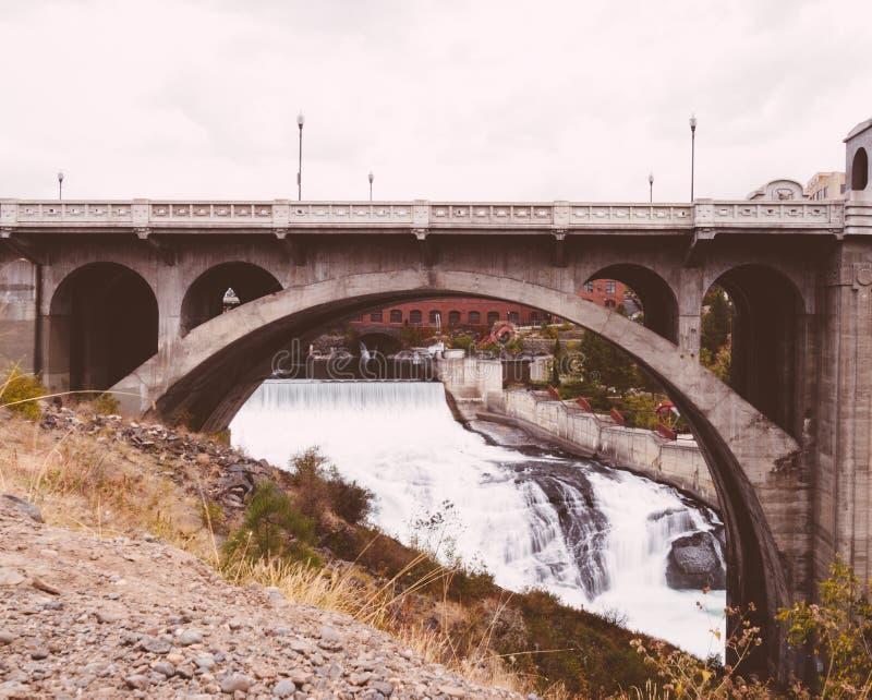 Pequeño río con una cascada que va debajo de un puente de piedra en una ciudad foto de archivo libre de regalías