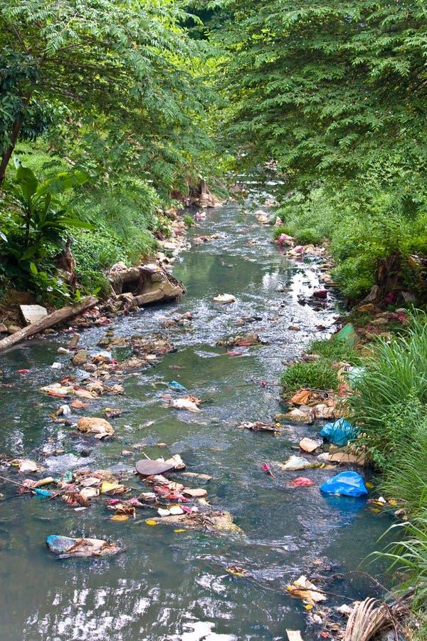 Pequeño río contaminado con basura fotografía de archivo