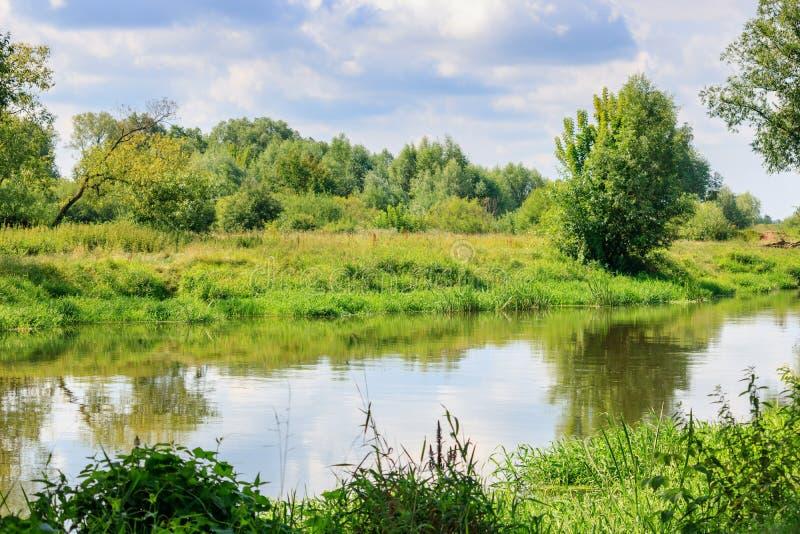 Pequeño río en el fondo de los bancos hierba-cubiertos contra el cielo nublado en el día de verano soleado Paisaje del río foto de archivo