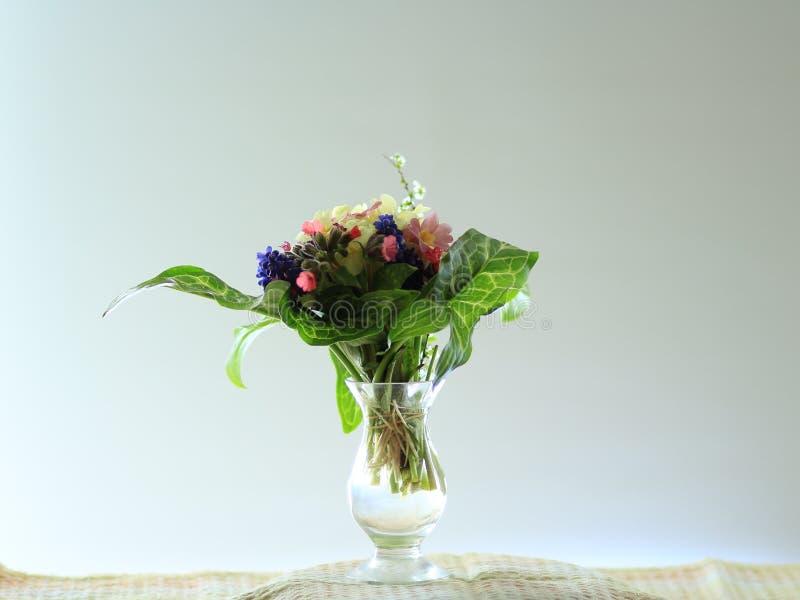 Pequeño ramillete de las flores de la primavera en un florero de cristal en un alféizar fotos de archivo libres de regalías