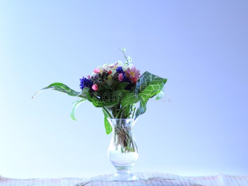 Pequeño ramillete de las flores de la primavera en un fondo azul claro imagenes de archivo
