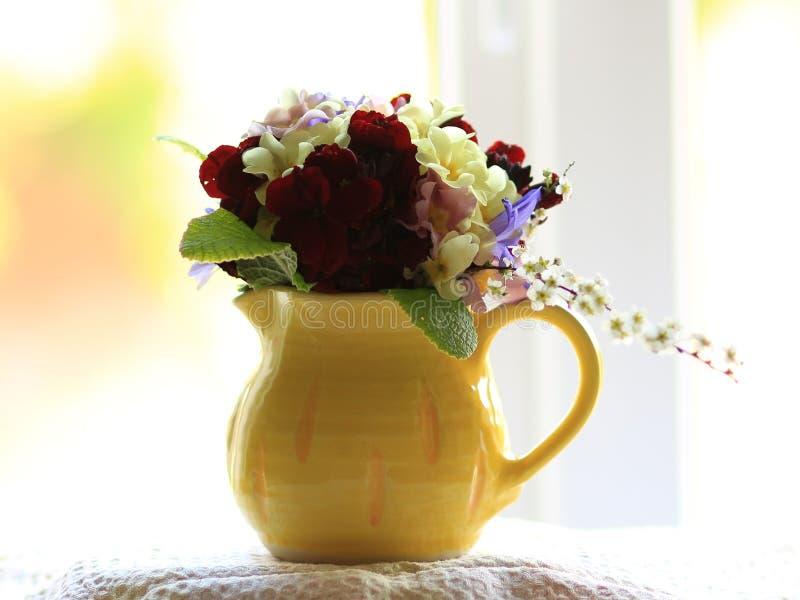 Pequeño ramillete de las flores de la primavera en un jarro pequeño, amarillo en un alféizar fotografía de archivo