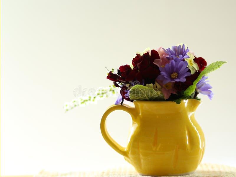 Pequeño ramillete de las flores de la primavera en un jarro pequeño, amarillo en un alféizar foto de archivo libre de regalías