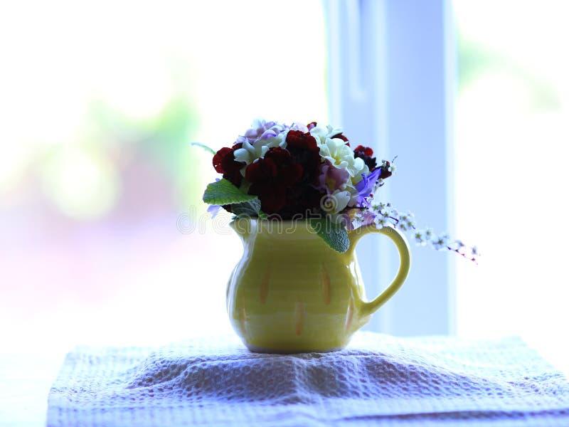 Pequeño ramillete de las flores de la primavera en un jarro pequeño, amarillo en un alféizar fotos de archivo libres de regalías