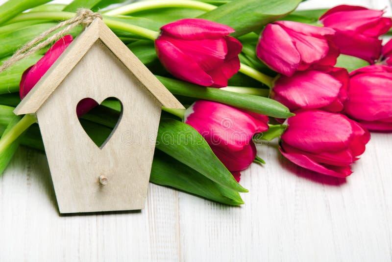 Pequeño ramo de madera de la casa y del tulipán en el fondo de madera blanco, imagenes de archivo