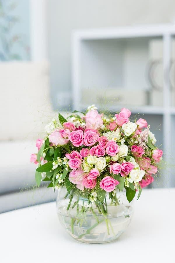 Pequeño ramo hermoso con las rosas en el florero de cristal imagenes de archivo