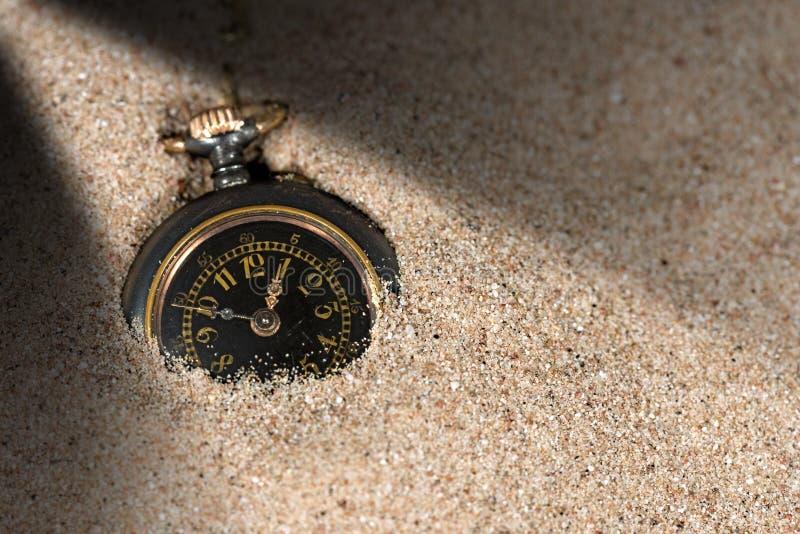 Pequeño reloj de bolsillo en la arena fotos de archivo libres de regalías