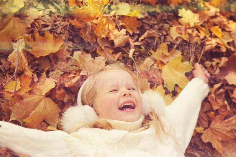 Pequeño retrato rubio de la muchacha que miente en las manos extendidas y la sonrisa de las hojas de arce del amarillo del otoño imagenes de archivo