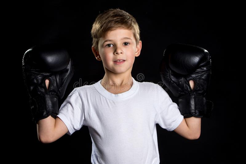 Pequeño retrato sonriente del combatiente del boxeador en guantes de boxeo negros con las manos para arriba El pequeño ganador fotografía de archivo
