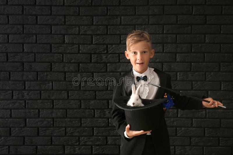 Pequeño sombrero lindo de la tenencia del mago con el conejo contra la pared de ladrillo oscura fotografía de archivo