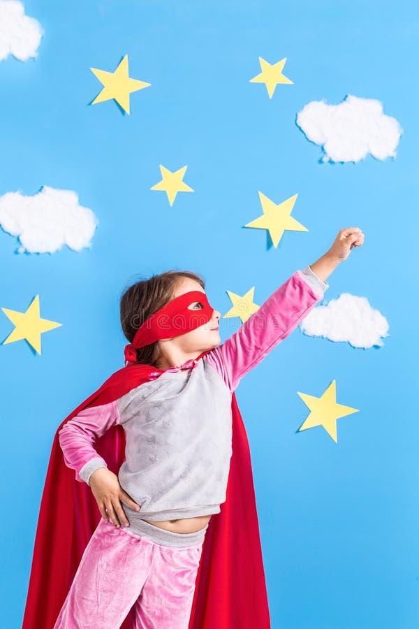 Pequeño super héroe de los juegos de niños Embrome en el fondo de la pared azul brillante con las nubes y las estrellas blancas C fotografía de archivo