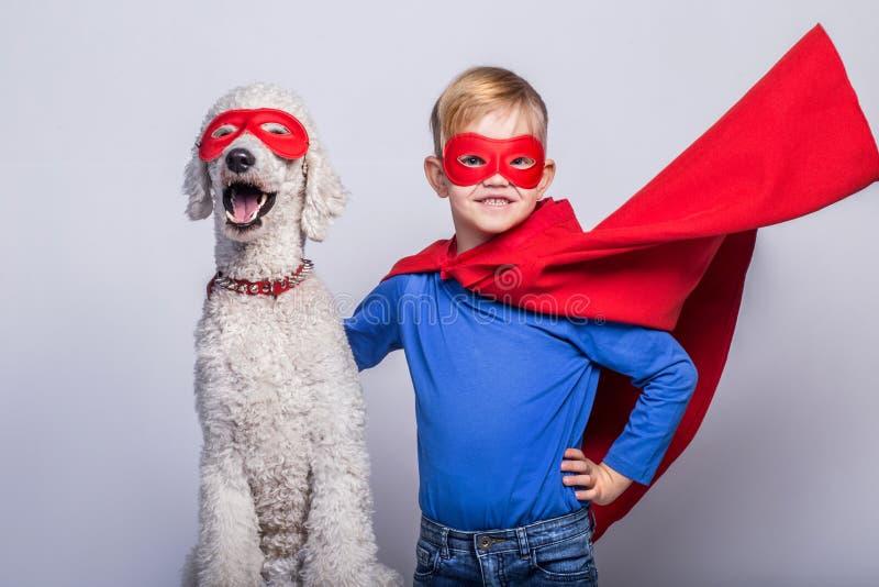 Pequeño superhombre hermoso con el perro superhero Víspera de Todos los Santos Retrato del estudio sobre el fondo blanco foto de archivo