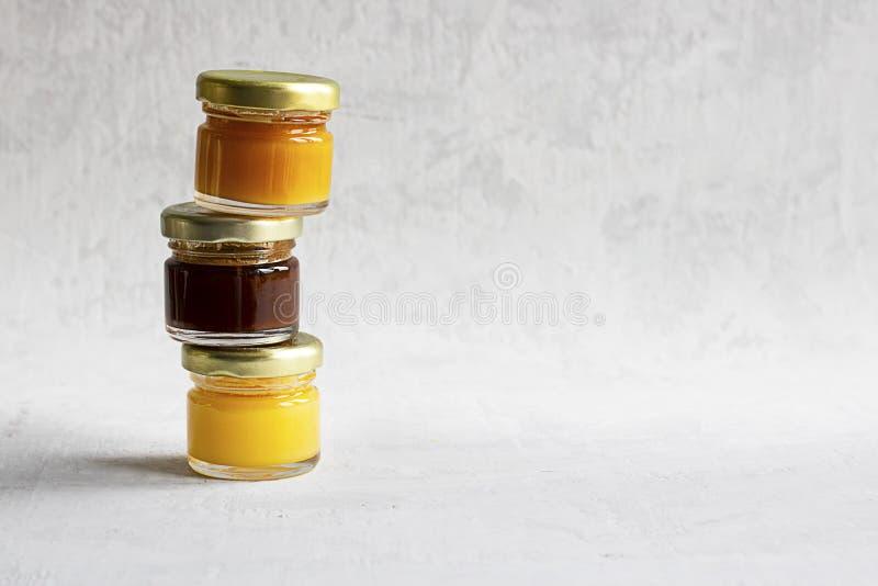 Pequeño tarro de cristal tres con el casquillo del metal con la miel marrón amarilla clara, anaranjada y oscura una en otro aisla imágenes de archivo libres de regalías