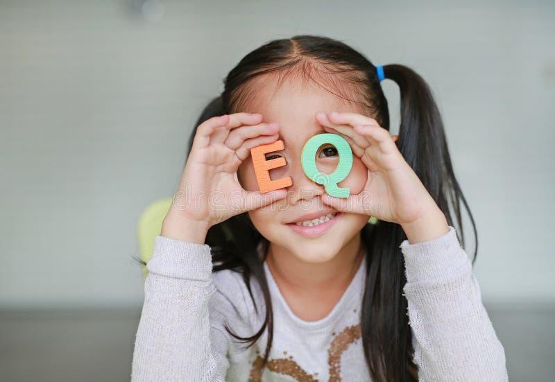 Pequeño texto emocional asiático lindo del cociente del alfabeto EQ de la tenencia de la muchacha del niño en su cara Concepto de fotografía de archivo