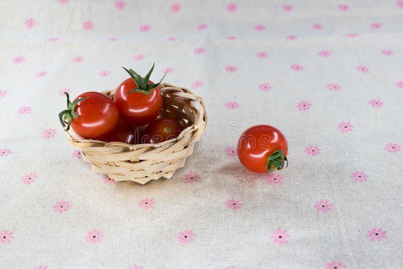 pequeño tomate en la cesta en fondo de la tabla fotos de archivo