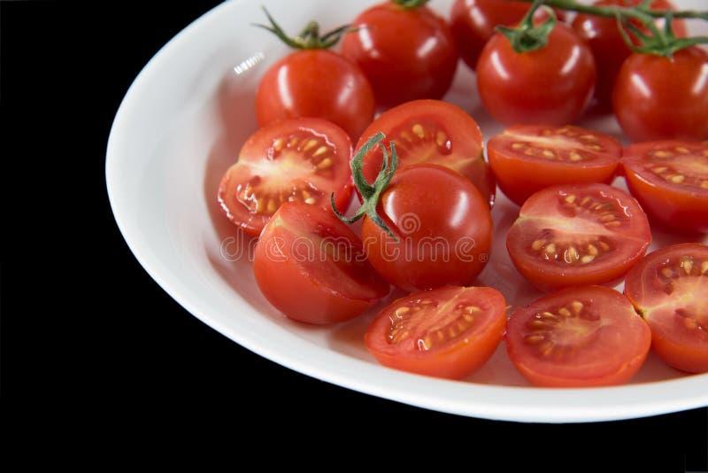 Pequeño tomate en plato con el fondo negro fotos de archivo libres de regalías