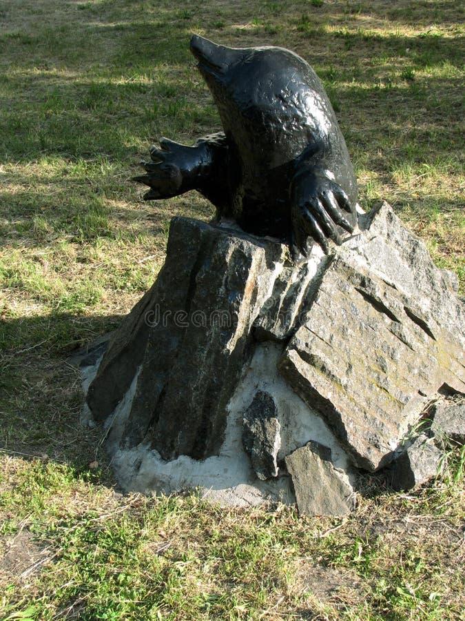 Pequeño topo de la escultura de bronce del parque, mirando hacia fuera del agujero de piedra fotografía de archivo