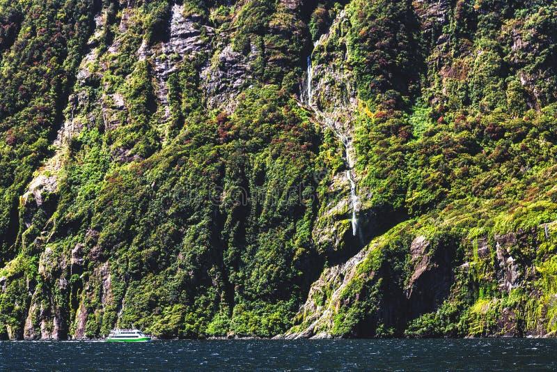 Pequeño transbordador de la travesía y alta cascada en Milford Sound, Nueva Zelanda imagen de archivo