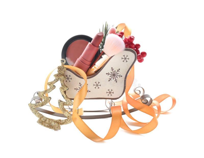 Pequeño trineo de la Navidad con los cosméticos decorativos en el fondo blanco imagen de archivo libre de regalías