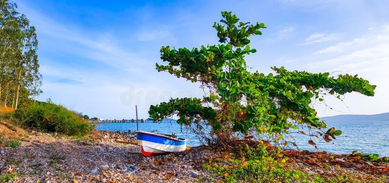 Pequeño uso del barco de la fibra de vidrio para pescar o navegar deporte en la playa de la roca imagen de archivo