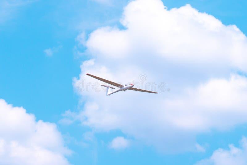 Pequeño vuelo del planeador contra el cielo azul y las nubes imágenes de archivo libres de regalías