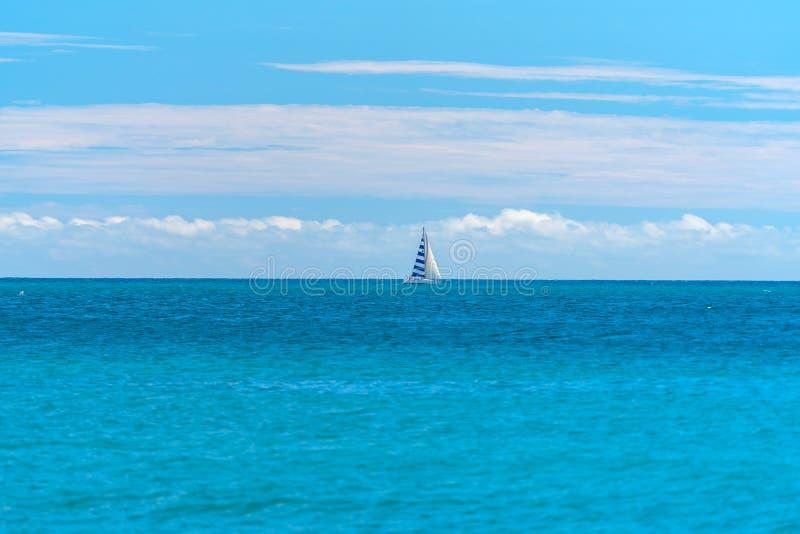 Pequeño yate debajo de la vela en el mar abierto imagenes de archivo