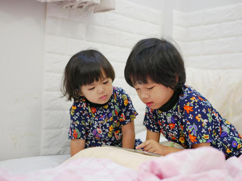 Pequeños años de los bebés, de las hermanas, 2 y 3, distribución/mirando un smartphone al gether - bebés que aprenden compartir fotografía de archivo