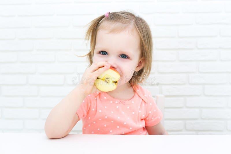 Pequeños 2 años lindos de muchacha con la manzana en casa imagen de archivo