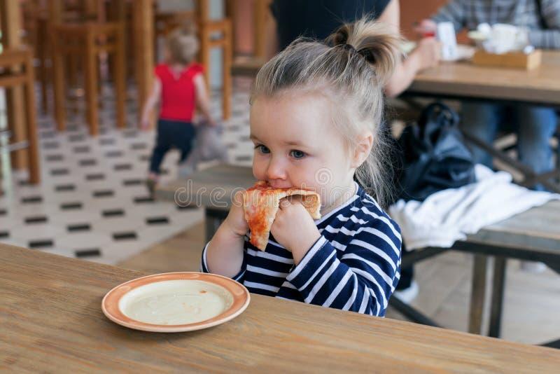 Pequeños 2 años lindos de muchacha que come la pizza en el restaurante imágenes de archivo libres de regalías