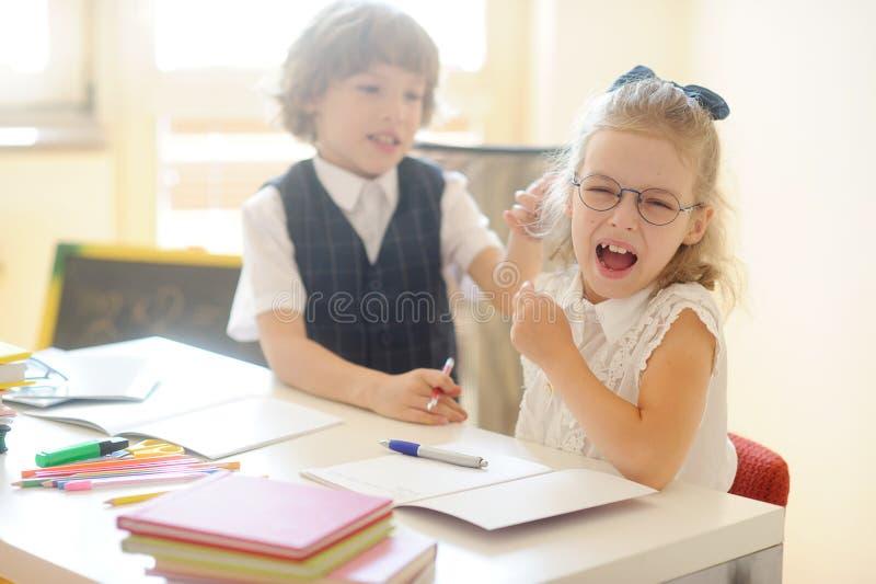 Pequeños alumnos, muchacho y muchacha, sentándose en su escritorio foto de archivo