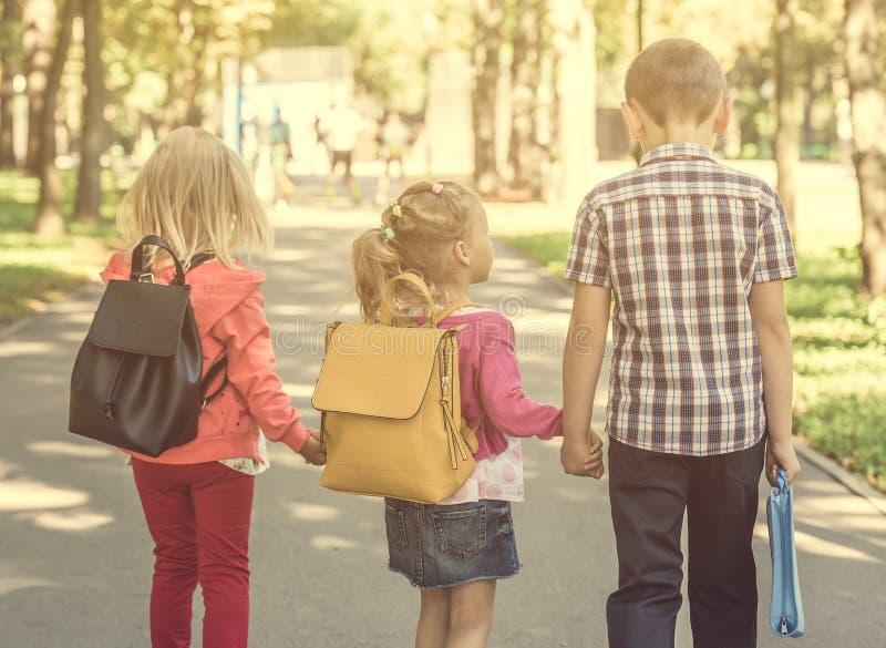Pequeños alumnos que caminan a casa de escuela imagenes de archivo