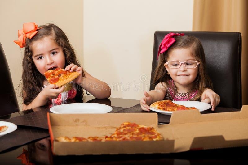 Pequeños amigos que comen la pizza foto de archivo