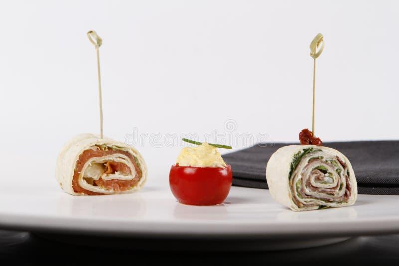 Pequeños aperitivos con el tomatoe llenado y las tortillas envueltas imagen de archivo