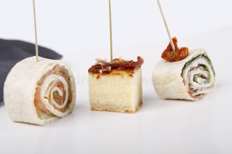 Pequeños aperitivos con los salmones, el jamón y el pastel de queso fotografía de archivo
