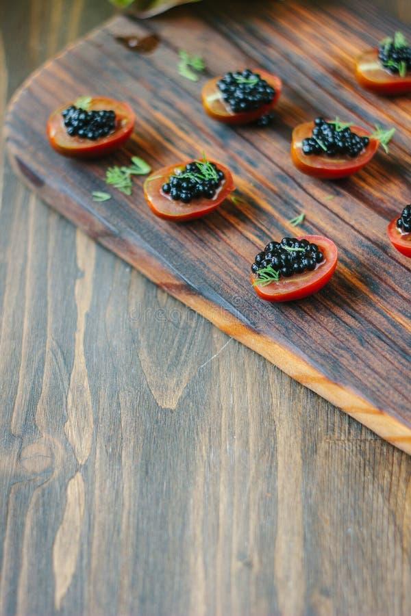 Pequeños aperitivos con los tomates de cereza y el caviar negro foto de archivo libre de regalías
