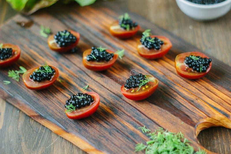 Pequeños aperitivos con los tomates de cereza y el caviar negro fotografía de archivo libre de regalías